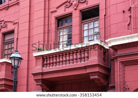 red house with a balcony windows