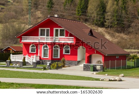 Red house with a white balcony