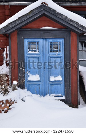 Red house with blue doors in winter - stock photo