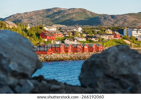 Red houses facades reflecting on the bay of Alta, Norway - stock photo