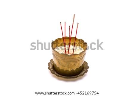 Red incense sticks in old golden incense burner on white background. - stock photo