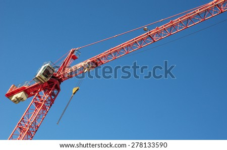 Red industrial construction crane against blue sky with copy space - stock photo