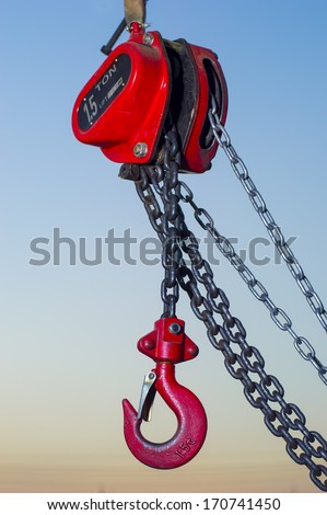 red Industrial hook hanging on reel chain and blue sky sunset background - stock photo