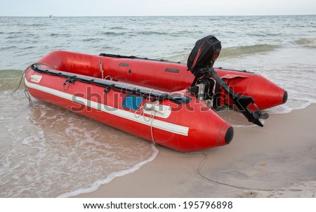 Red inflatable boat on beach - stock photo