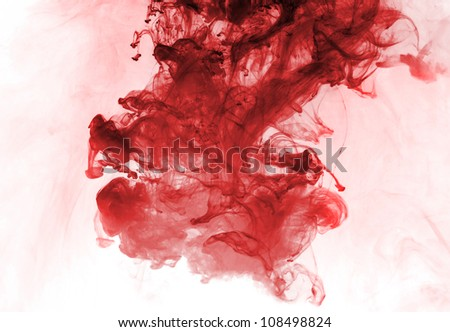Red ink in water on a white background. - stock photo