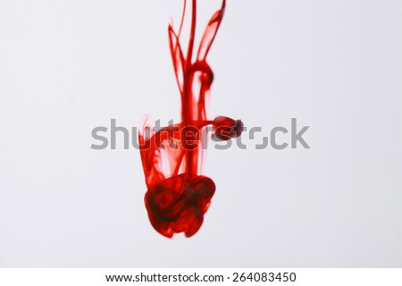 Red ink  liquid in water making abstract forms - stock photo