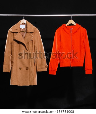 Red jacket and coat hanging on hanger - stock photo
