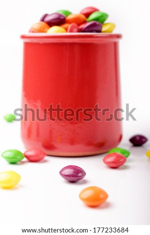 Red jar with colorful candies on a white background - stock photo