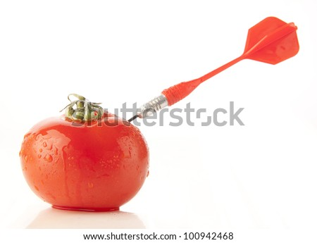 red javelin stuck in the red tomato - the idea of success in the affairs of hitting the target address issues and concerns - stock photo