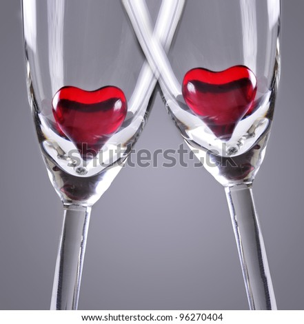 Red jelly hearts in champagne flutes, grey background - stock photo