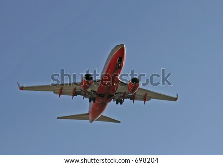 Red jet airplane coming in for a landing - stock photo