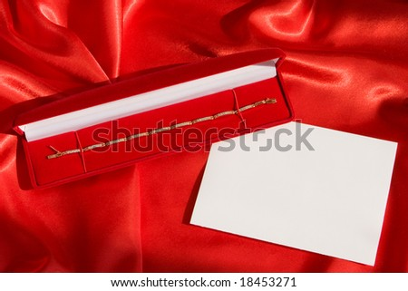 Red jewerly  box with gold bracelet and empty card on red satin