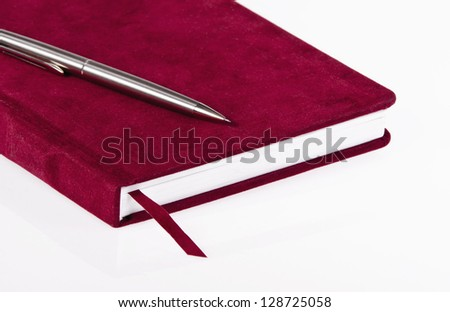 Red journal and a pen over white background - stock photo