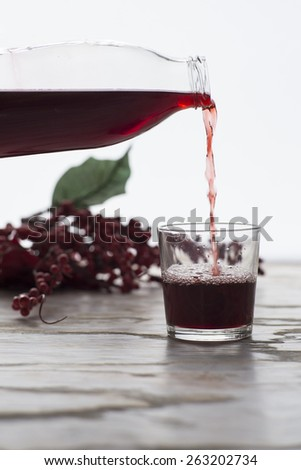Red juice is poured into a glass - stock photo