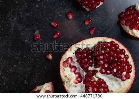 Red juicy pomegranate on dark marble background. Healthy, antioxidant, fresh, gourmet, delicious, organic fruit. Ingredient for grenadine. Close-up and copy space. - stock photo