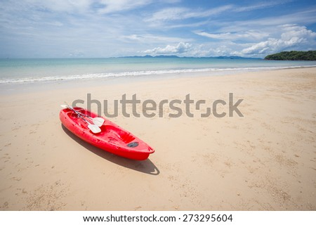 Red kayak at the ocean beach during low water - stock photo