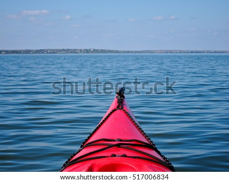 Red kayak in the lake with open view on calm blue water