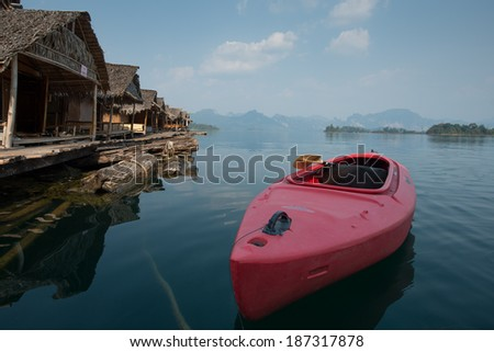Red kayak on Rachapapha dam. Khao Sok National Park. Thailand. - stock photo