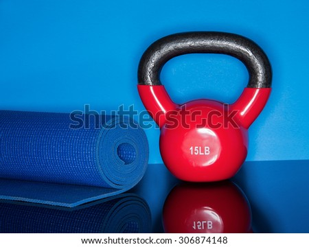 Red Kettle ball on blue background with mat roll - stock photo