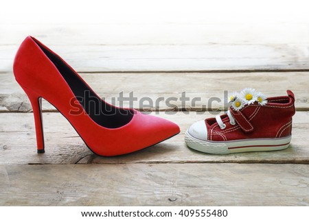 red kids sneakers with a bouquet of daisies and mum's red high heels on rustic wooden planks, concept for mother's day, background fades to white - stock photo
