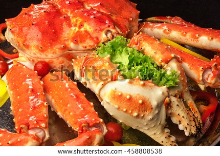 Red king crab served on big plate with salad leaves, pepper slices, cherry tomatoes. Front view.
