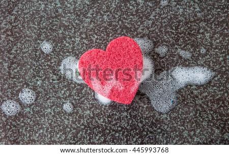 Red kitchen sponge in a heart shape on dark background - stock photo