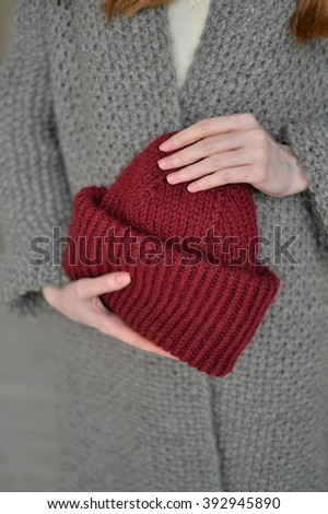 Red knitted cap in her hand - stock photo
