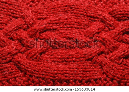 Red knitted cloth is made by hand. It is decorated with bulging braid. - stock photo
