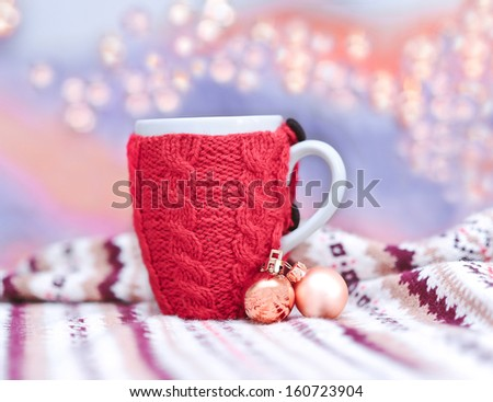 Red knitted cup with christmas decorations and holiday lights - stock photo