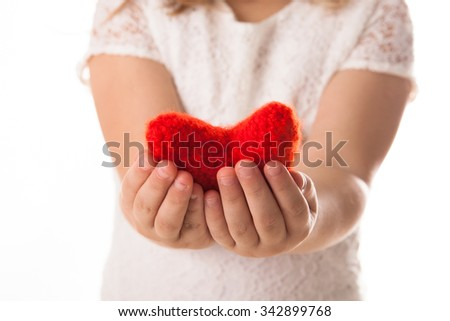Red knitted heart in the hands of children, the concept of Valentine's Day, White Background,diagonal