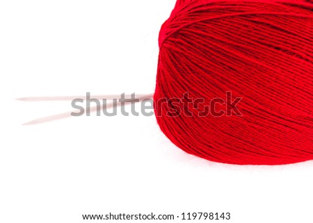 Red knitting yarn with needles isolated on white