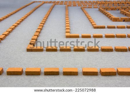Red labyrinth, composed of many bricks on a gray floor - stock photo