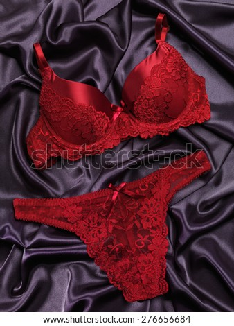 Red lacy lingerie womens underwear on black background - stock photo