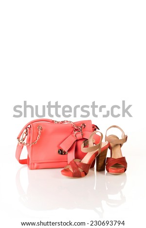 Red lady's high heeled shoes and handbag isolated on a white studio background
