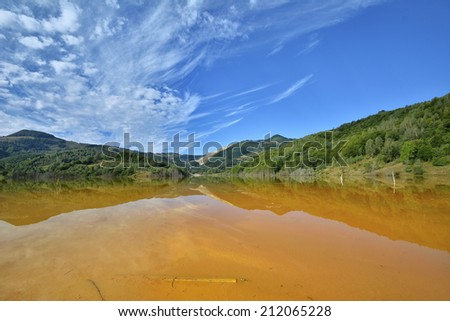 Red lake polluted with dead trees and a flooded church in Romania, Geamana - stock photo