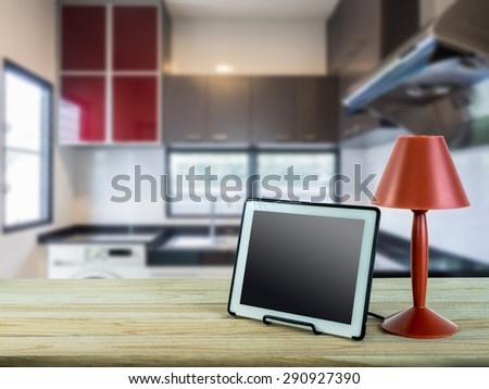 Red lamp, tablet on wooden counter top with modern kitchen blurry background - stock photo
