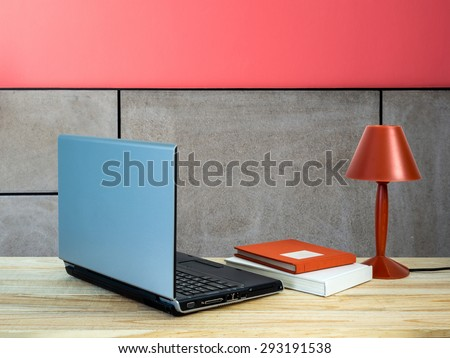 Red lamp with laptop computer, books on wooden table top over modern wall background/ interior still life - stock photo
