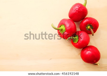 Red lantern hot ripe habanero hot chili pepper from caribbean or mexico. over wooden table background - stock photo