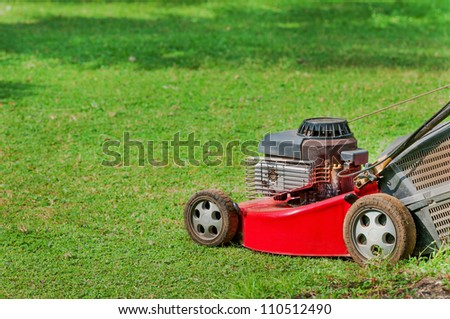 Red lawn mower on green grass in sunny day - stock photo