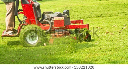 Red lawnmower on green grass - stock photo