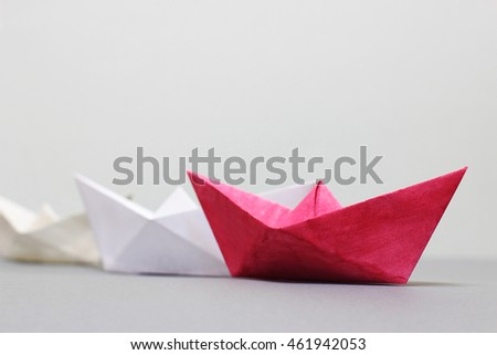 Red leader paper boat leading white ones on light gray background. Shallow depth of field. Leadership, management, teamwork and competition concept