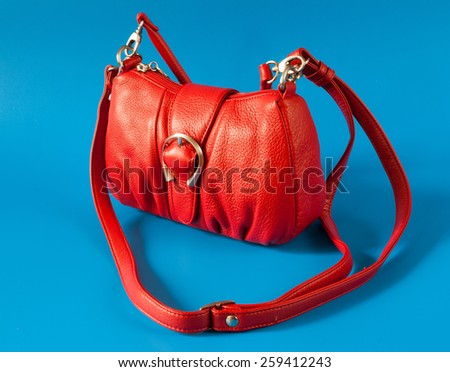 Red leather bag on the blue background.
