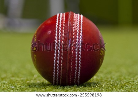 Red Leather Cricket Ball With Stitching On Turf - stock photo