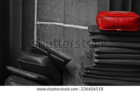 Red leather cushion on top of a stack of monochrome cushions - stock photo