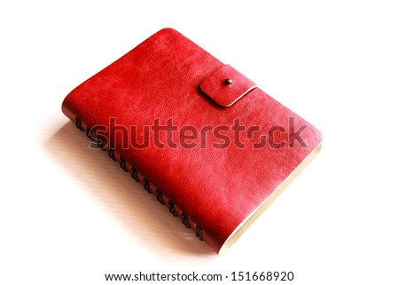 Red leather notebook on white background - stock photo