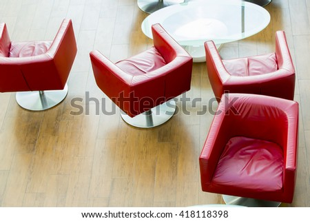 Red leather red armchair and white table at waiting room. - stock photo