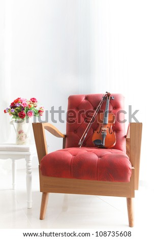 red leather wood arm chair with violin in white room - stock photo