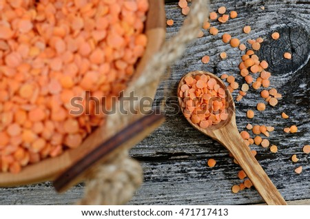 red lentil in spoon on wooden table