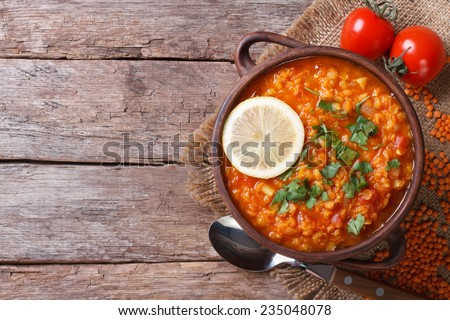 red lentil soup with lemon and vegetables close-up on the table. horizontal view from above - stock photo