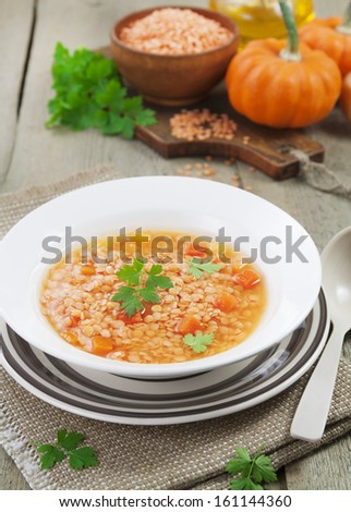 Red lentil soup with vegetables in the plate on the table - stock photo